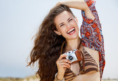 Smiling bohemian young woman with retro photo camera on beach Stock Image
