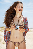 Smiling bohemian young woman with retro photo camera on beach Royalty Free Stock Photo