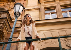 Smiling boho chic with sunglasses near old town streetlight Royalty Free Stock Photos