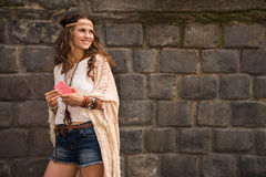 Smiling boho young woman near stone wall looking on copy space Royalty Free Stock Photo