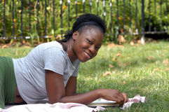 Smiling with a book. Young afican american lady looks up from a book and smiles royalty free stock images
