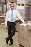 Smiling boss leaning on stack of cartons Royalty Free Stock Photography