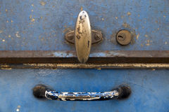 Closeup of a blue painted rusty metal tool box. Closeup of the lid of a rusty blue metal tool box. The two handles and the key hole form a smiling face royalty free stock photo