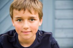 Smiling boy. Portrait of a smiling boy in front of a wooden wall Royalty Free Stock Photo