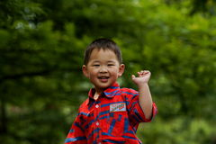 Smiling boy. A cute Chinese boy smiling and waving in a sunny summer day Royalty Free Stock Images