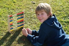 Smiling boy with an abacus. Smilling little boy lying by the colorful abacus royalty free stock image
