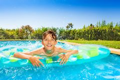 Smiling boy with air mattress in swimming pool royalty free stock images