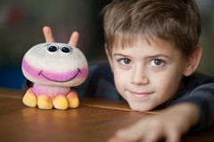 Smiling Boy and Alien Toy  with Antennas. Boy with a toy at the table Royalty Free Stock Photos