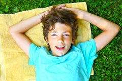 Smiling boy with arms under head lay Royalty Free Stock Images