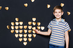 Smiling boy assembling  golden heart Royalty Free Stock Images