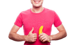 Smiling boy with banana shows OK. Smiling handsome guy holding yellow banana and showing ok (thumb up) near his stomach over white background. studio shot stock photos