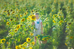 A smiling boy with a basket of sunflowers. Smiling boy with sunflower. A cute smiling boy in a field of sunflowers. royalty free stock image