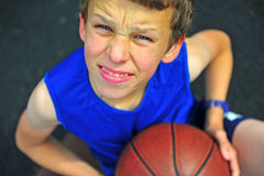 Smiling boy with a basketball sitting on court Royalty Free Stock Image
