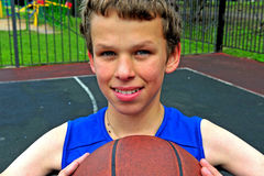 Smiling boy with a basketball sitting on court Royalty Free Stock Photos