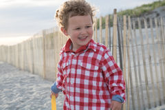 Smiling Boy on Beach in Front of Wooden Fence. A happy young child is holding a pail on the beach. He is in front of the sand dune fence, walking into the beach royalty free stock images