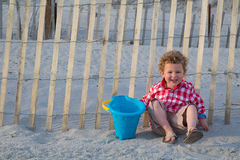 Smiling Boy on Beach in Front of Wooden Fence. A happy young child is holding a pail on the beach. He is in front of the sand dune fence, walking into the beach stock photo