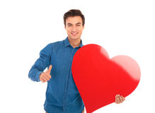 Smiling  boy with big red heart showing the ok sign. Smiling casual boy with big red heart showing the ok sign on white background Stock Photos