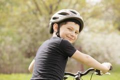 Smiling boy on bike. Looking over shoulder Royalty Free Stock Images