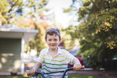Smiling Boy on Bike at Home. Young boy riding a bicycle in the front yard of a suburban house Stock Images