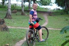 Smiling boy on bike stock image