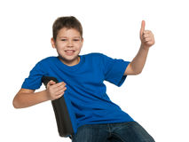 Smiling boy in blue shirt holding his thumb up Stock Photo