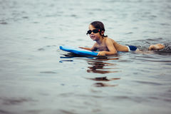 Smiling boy on bodyboard in water Stock Photography