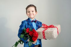 Smiling boy with bouquet of flowers and a gift on a light background stock photo