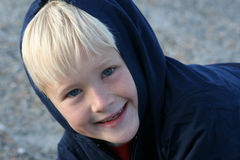 Smiling Boy Bundled up in Clothing at the Beach. Six year old blond boy bundled up in clothing for a cool winter day at the beach. natural light Stock Photo