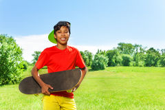 Smiling boy in cap and with skateboard portrait Royalty Free Stock Photo