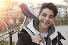 Boy carrying push bike. Smiling boy carrying push bike outdoors royalty free stock photo