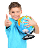 Smiling boy in casual  holding globe with thumbs up Royalty Free Stock Image