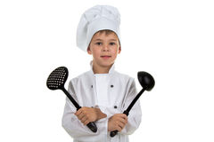 Smiling boy in chef uniform holding kitchen equipment, on white background. Smiling boy wearing chef uniform holding kitchen equipment, isolated on white Royalty Free Stock Images