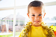 Smiling boy with Christmas garland Stock Photos