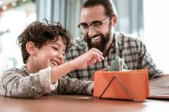 Smiling dark-haired preschool boy sitting near his loving father royalty free stock photography