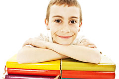 Smiling boy with colored school books on the table Stock Photos
