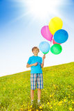 Smiling boy with colorful balloons stand in field Royalty Free Stock Photography