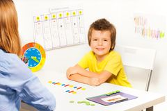 Smiling boy with colorful coins in order Stock Photo