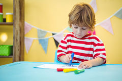 Smiling boy colouring some paper. At the desk stock photos