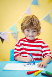 Smiling boy colouring some paper Royalty Free Stock Images