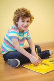 Smiling boy colouring some paper. On the floor Royalty Free Stock Photography