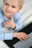 Smiling Boy And Computer. Smiling young boy laying in front of a computer keyboard, with one hand on the keys royalty free stock photos
