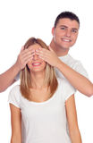 Smiling boy covering his girlfriend's eyes to surprise him Royalty Free Stock Photos