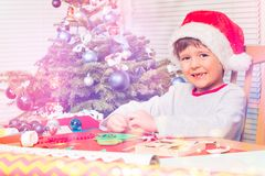 Smiling boy decorating paper Christmas tree stock photography