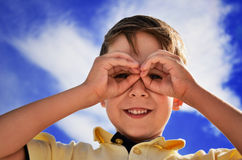 Smiling boy did fingers like binoculars Royalty Free Stock Photography
