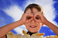 Smiling boy did fingers like binoculars Royalty Free Stock Photography
