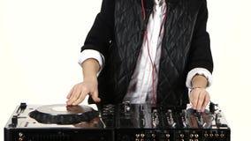 Smiling boy dj in headphones playing on vinyl. White background stock video