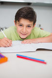 Smiling boy doing homework in kitchen Royalty Free Stock Images