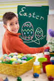 Smiling boy draws easter eggs with chalk on  green chalkboard Stock Image