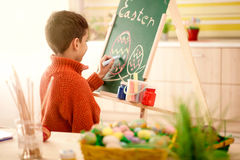 Smiling boy draws easter eggs with chalk on  green chalkboard Royalty Free Stock Photos
