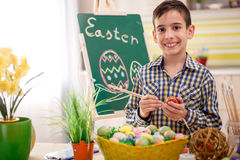 Smiling boy draws easter eggs Royalty Free Stock Photos